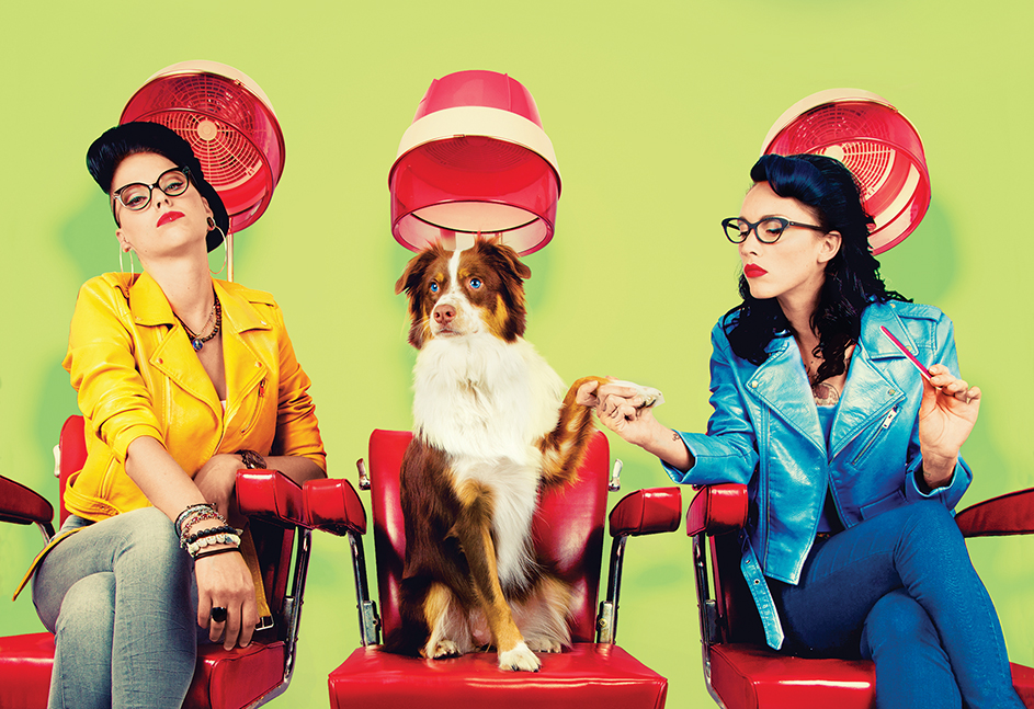 Two women and a dog sitting in hair salon chairs